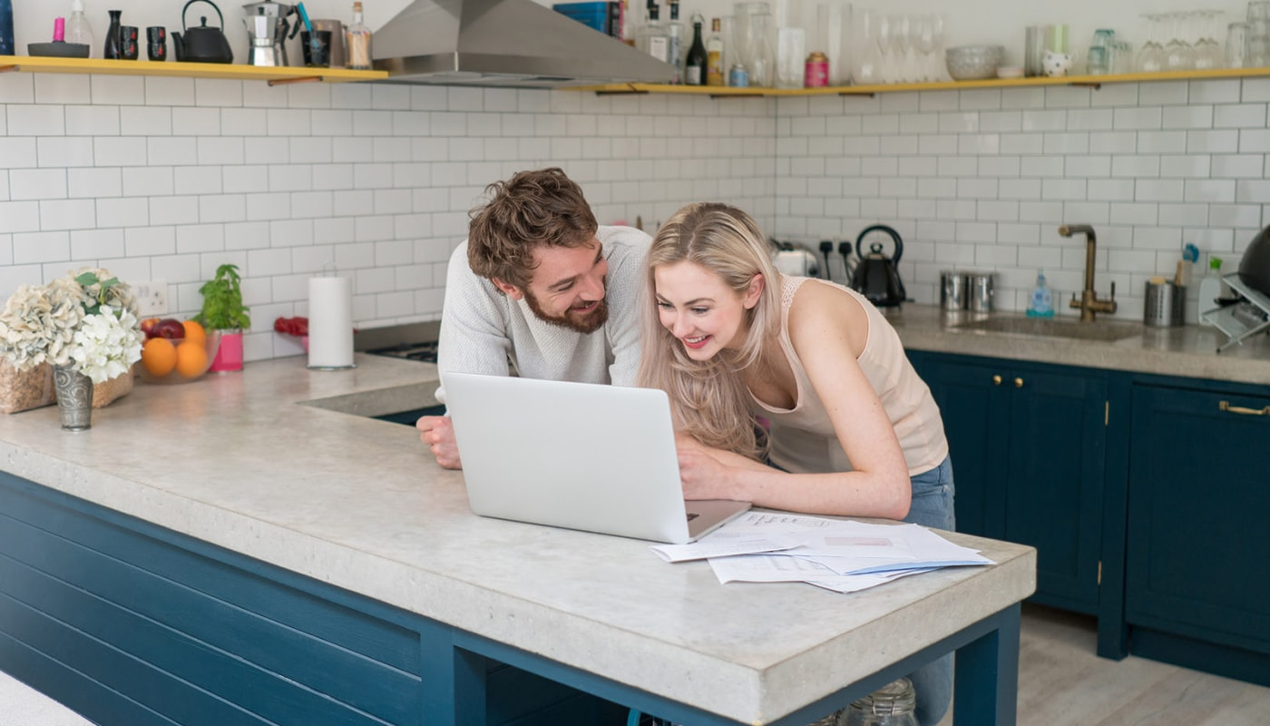 Young couple at home using a laptop computer and looking very happy looking at credit history together and discussing credit score