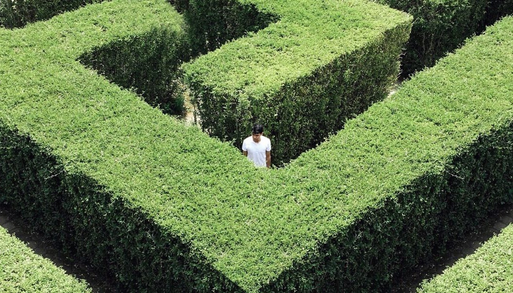 Someone confused and lost in a maze. Like choosing whether to invest or pay down student loan debt.