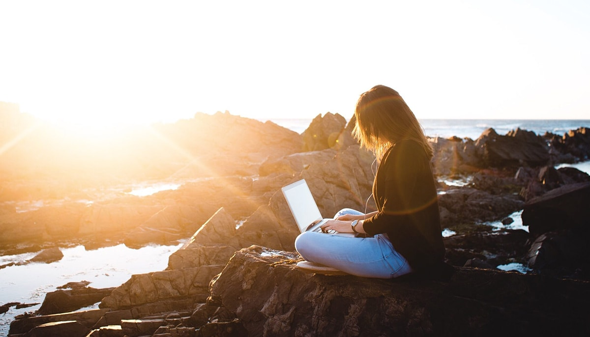 Girl looking to complete her FAFSA application before deadline while outside enjoying the sun and ocean.