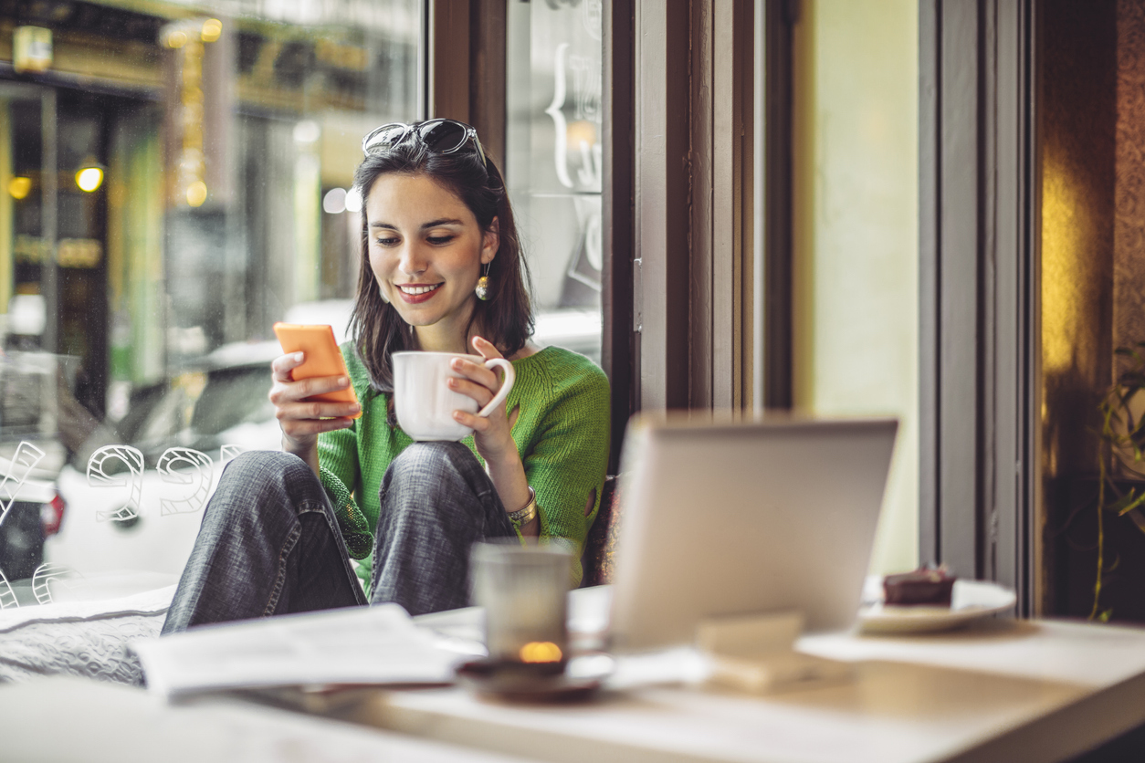 young woman budgeting by tacking spending in coffee shop