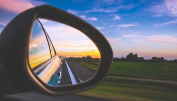 looking back in rear view mirror