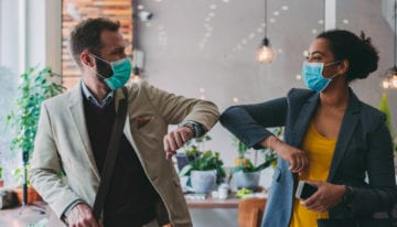 Colleagues touching elbows as they return to the office following the COVID-19 pandemic.