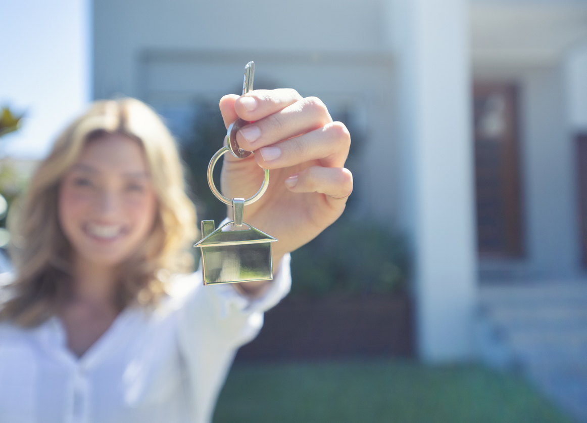 Young woman holding keys to first home