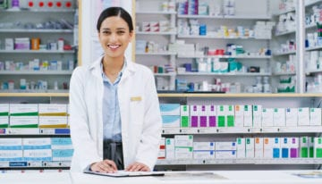pharmacist smiling after refinancing student loans