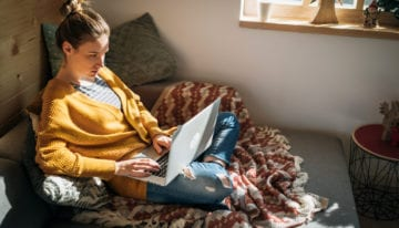 young woman researching student loan refinancing requirements