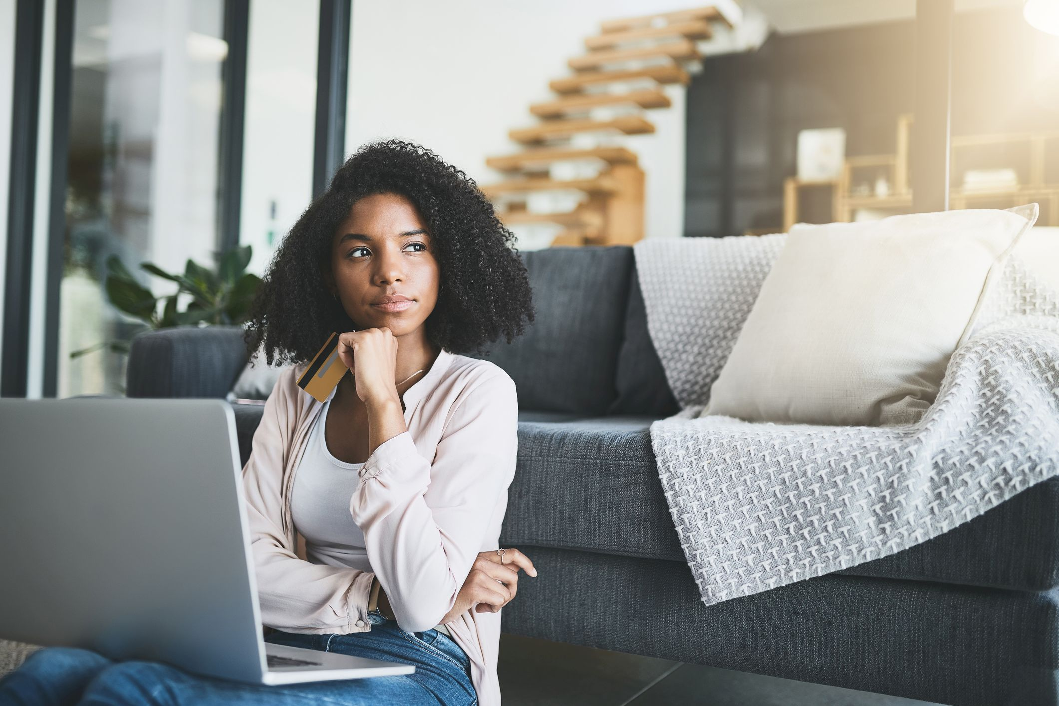Woman thinking about using credit card to pay down student loans