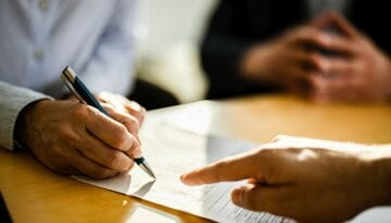 Cosigner signing student loan paperwork
