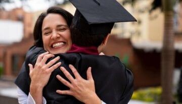 Parent hugging son at college graduation