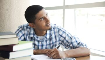 Young man considering whether student loans are worth it
