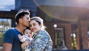 Military spouse hugging his family
