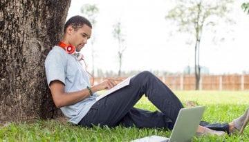 man student sitting under tree