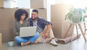 young couple using a laptop in living room with boxes