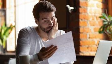 Young man looking at debt