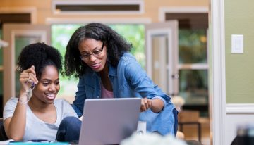 Mom and daughter reading private and federal student loan eligibility requirements