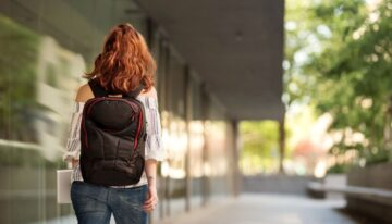 young female university student with backpack
